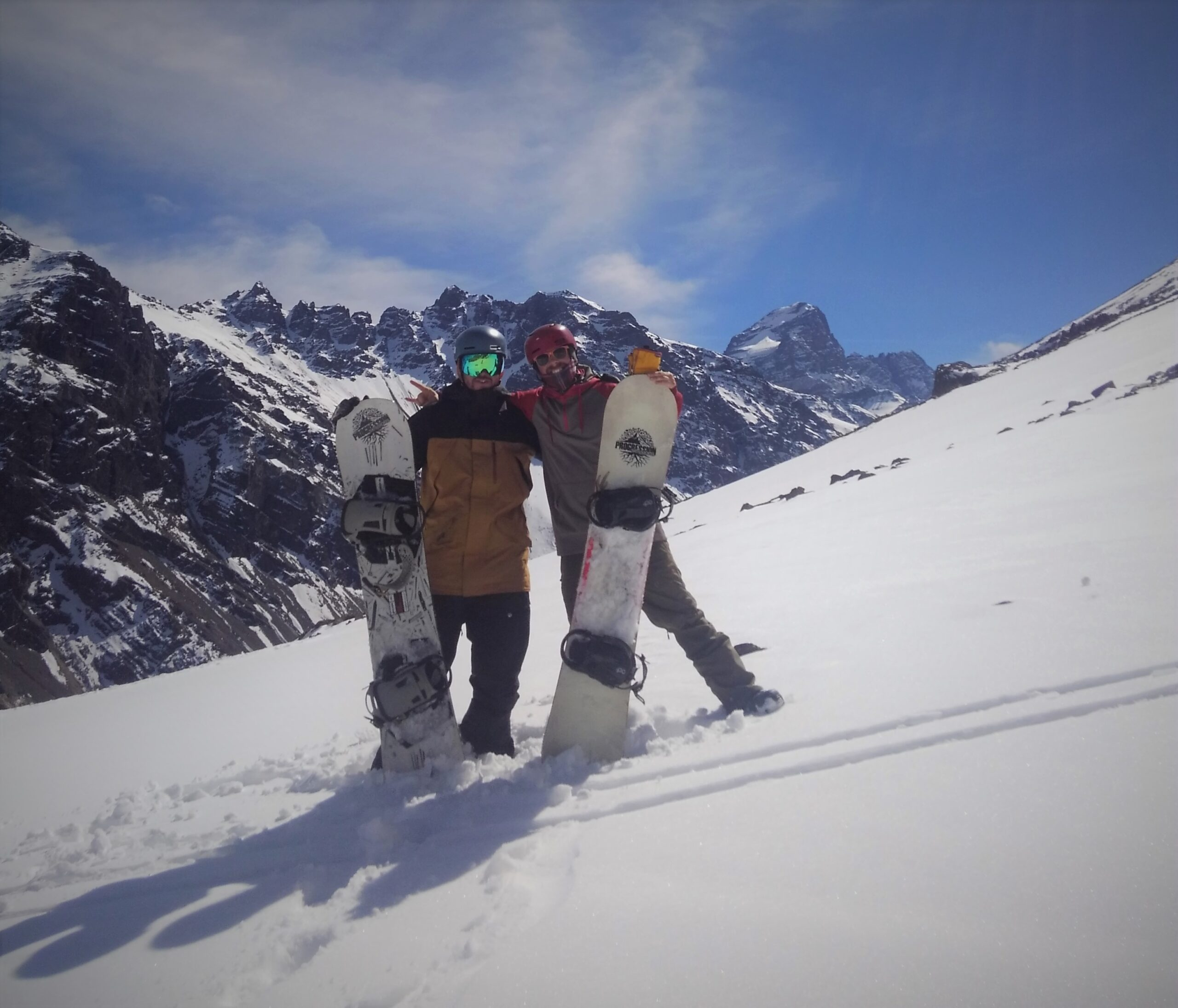2 men holding snowboards on side of snow covered mountain with mountains in the background